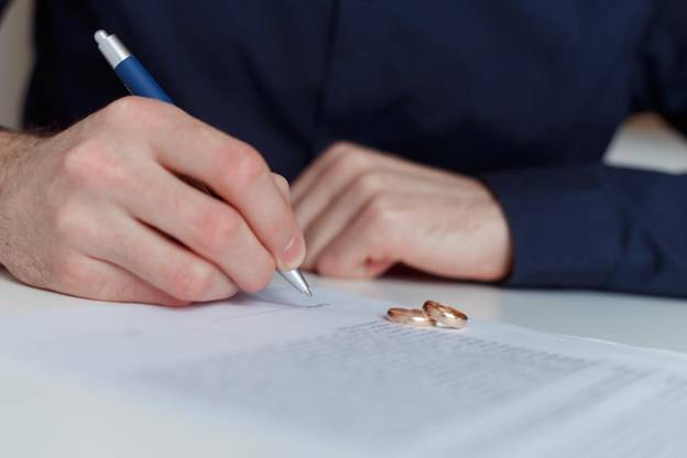 A man signing divorce documents