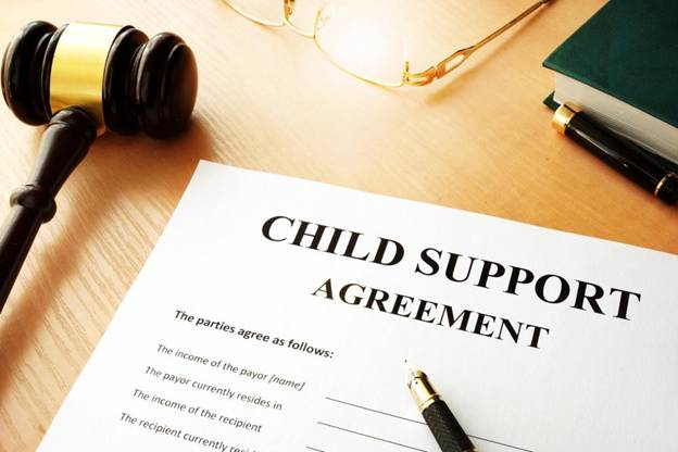 Child support agreement on a table with glasses and gavel